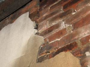 Unsecured stucco separating from the brick substrate